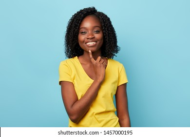 positive good looking stylish woman in yellow T-shirt with finger on her chin posing to the camera. close up portrait. studio portrait.