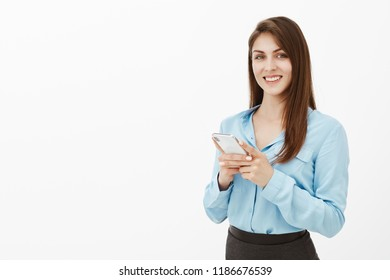 Positive good-looking brunette in office clothes, holding smartphone and gazing at screen, being satisfied with great workability of new gadget, using app to communicate with foreign friends
