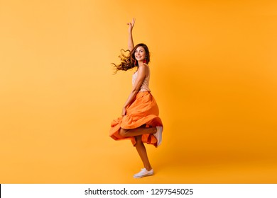 Positive good-looking girl funny dancing on yellow background. Magnificent white woman in long orange skirt jumping with sincere smile.