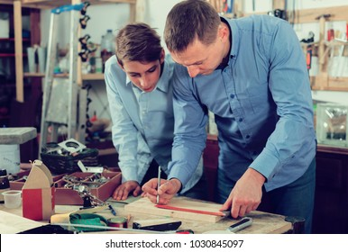 positive greek adult father teaching son �arpentry in the garage