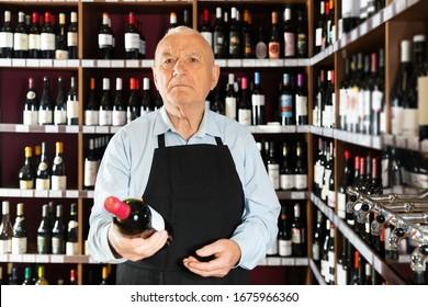 Positive grey-haired elderly vintner offering wine in modern wineshop
