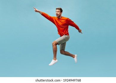 Positive guy with beard in bright cool clothes and white modern sneakers looking away and jumping on isolated blue background. .
