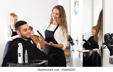 Positive guy cuts hair and female barber at the hair salon. Focus on the man