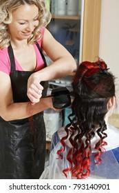 Positive hairdresser curling hair of caucasian woman with curler. Vertical closeup shot