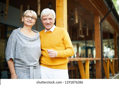 Positive handsome gray-haired senior man in yellow sweater embracing beloved girlfriend wearing gray dress, they standing on porch and smiling at camera