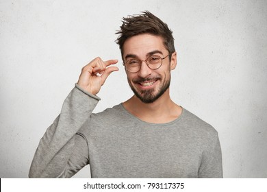Positive handsome man with stylish hairdo, dressed in casual sweater, shows something very tiny or small, being in good mood, poses against white concrete background. Young fashionable male gestures