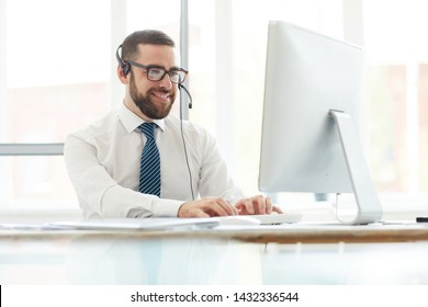 Positive handsome young switchboard operator in headset sitting at table and typing on computer keyboard while answering website message of customer