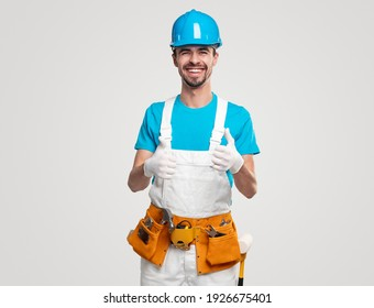 Positive handyman in overall and hardhat with toolkit showing thumbs up and smiling brightly against white background