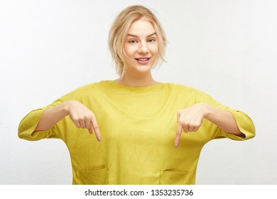Positive happy blonde girl in casual bright yellow clothes pointing to look down with both index fingers, smiling with interest isolated in white studio