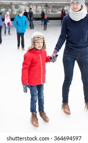 positive happy boy and his mother enjoying winter vacation at outdoor ice skating rink