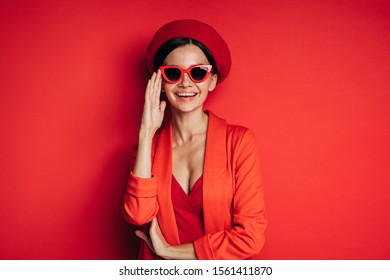 Positive, happy and cheerful young model posing on camera. Wear stylish fashionable red clothes. Look straight through sunglasses and smile. Fashio icon. Modern model .Isolated ovver red background