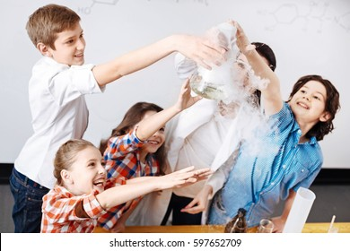 Positive happy children trying to touch a chemical flask