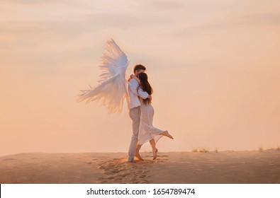 positive Happy Girl and angel hugging. man in white suit creative wings Princess long hair pink dress. Backdrop vanilla sky clouds, footprints in sand sunset desert. Dubai United Arab Emirates nature