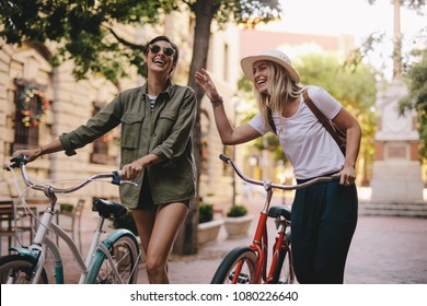 Positive and happy girls walking on the city street with bicycles. Female friends enjoying a walking down the street with their bikes.