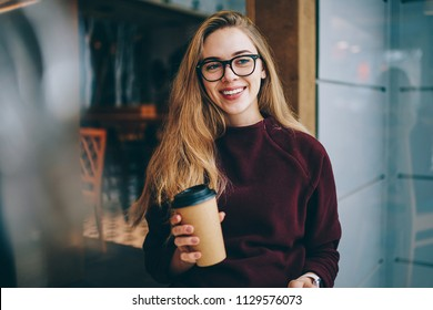 Positive happy hipster girl in eyewear sitting  at university cafeteria and waiting friend while drinking takeaway coffee indoors, successful woman casual dressed resting at campus and looking away