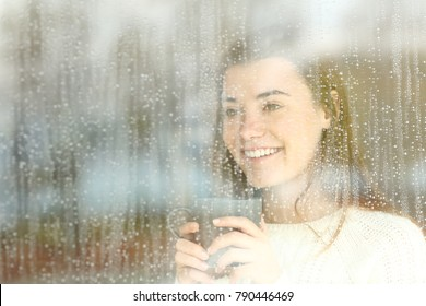 Positive happy teen looking through a window holding a coffee mug in a rainy day