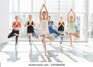 Positive happy young girls of yoga lovers doing vrikshasana standing on one leg in the bright gym against the background of a large window. Concept of group yoga and healthy lifestyle