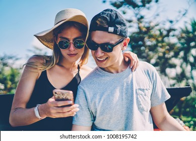 Positive hipster couple using application on smartphone for navigating during summer trip,trendy dressed male and female travelers searching information in networks browsing web page on mobile phone