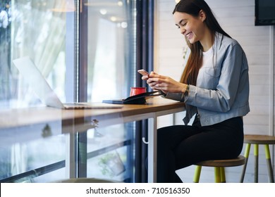 Positive hipster girl laughing and messaging with friends in social networks on digital mobile phone via high speed internet connection.Cheerful young woman received funny sms on modern telephone