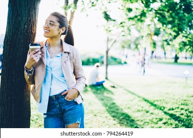 Positive hipster girl spending free time in park enjoying tasty coffee and favourite music from playlist.Good looking female listening song in radio broadcast in earphones standing near publicity area