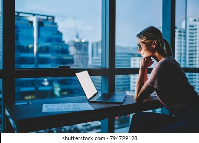 Positive hipster girl watching interesting movie online via high speed internet connection on modern laptop device spending evening leisure time in apartment.Blank copy space area of computer screen