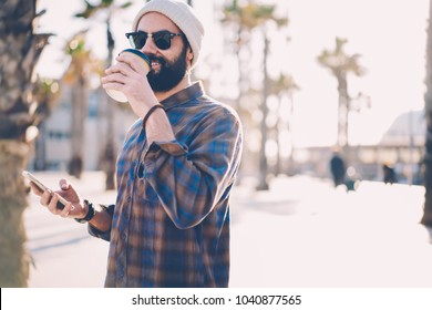 Positive hipster guy in hat and black sunglasses drinking coffee to go walking in urban setting with mobile phone in hand.Male blogger with beard enjoying hot beverage while installing app on cellular