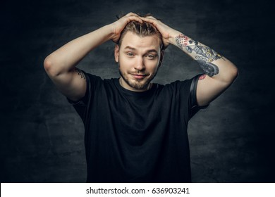 A positive hipster male dressed in a black t shirt holds head with tattooed arms.
