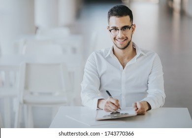 Positive HR employee sitting at a desk at an onboarding meeting with interns