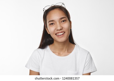 Positive human emotions, joy and happiness concept. Picture of attractive carefree young Chinese female wearing casual white t-shirt and round eyeglasses on her head, smiling broadly at camera