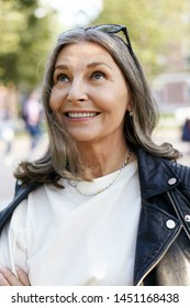 Positive human emotions and reaction. Beautiful stylish European female in her fifties having walk on nice sunny day, crossing arms on chest, smiling broadly and looking up, watching birds fly in sky