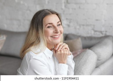 Positive human emotions, reaction, feelings and attitude. Gorgeous happy elderly European woman with loose hair and charming joyful smile, rejoicing at good positive news, sitting at home on couch