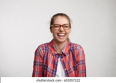 Positive human emotions. Studio portrait of relaxed carefree young woman with toothy smile wearing eyeglasses closing eyes tight while laughing out loud at good jokes, having fun with friends indoors
