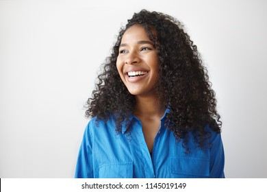 Positive human facial expressions, emotions, reaction and feelings. Attractive young dark skinned female with voluminous hairstyle laughing at joke, looking away, showing white perfect teeth
