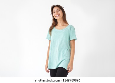 Positive human facial expressions, emotions, feelings and reaction. Beautiful happy young mixed race female with charming smile and loose brown hair posig in studio, dressed in blue oversize t-shirt