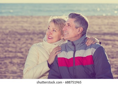 positive husband and wife spend time together happily at sea beach on bright day