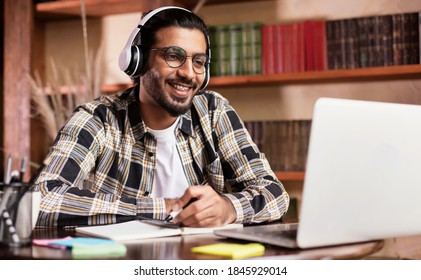 Positive Indian Student Guy At Laptop Computer Learning Online Having Remote Class With Distant Teacher Sitting At Home, Wearing Headphones. Modern Education, E-Learning And E-Teaching Concept