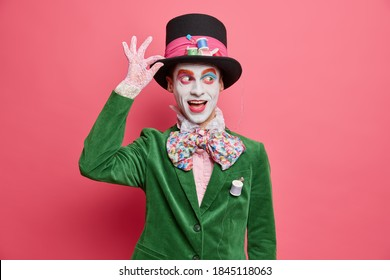 Positive insane hatter wears bright makeup ready for street performance or masquerade dressed in green costume and hat poses against rosy background. Happy halloween concept. Mysterious character