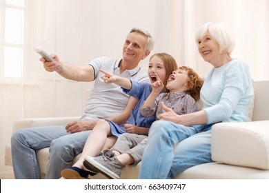 Positive inspiring couple having a lovely weekend with their grandchildren