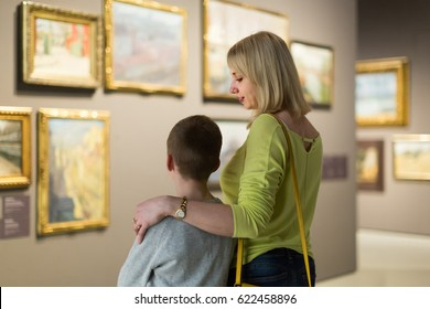 positive italian mother and son looking at paintings in halls of museum