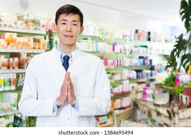 positive japanese specialist who is standing near table with cashbox in pharmacy.