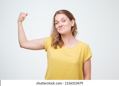 Positive joyful european woman showing hand muscles. Middle aged Caucasian woman in casual wear flexing bicep. Strength or feminism concept. I am strong enough to do it myself.