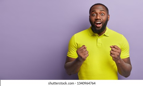 Positive joyous glad young man keeps eyes widely opened, hands clenched in fists, wears yellow bright t shirt, rejoices success, stands over purple wall with free space for your advertisement