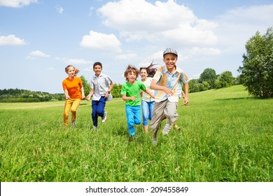 Positive kids play and run together in the field
