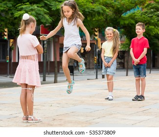 Positive kids in school age playing together with chinese jumping rope outdoors