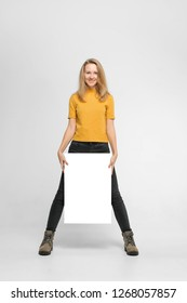Positive laughing woman wearing black jeans and yellow t-shirt with blondie hair, toothy smile is holding white big mockup poster near her legs isolated on white background