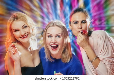 Positive laughing women blowing party whistles during New Year celebration