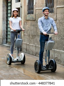 Positive laughing young  boy and girl posing on segways in vacation on city street