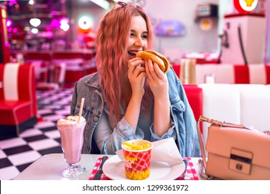 Positive lifestyle portrait of happy exited pretty woman with pink hairs having dinner at vintage American cafe, eating hot dog, french fries and mil shake, junk food cheat meal, pastel colors.