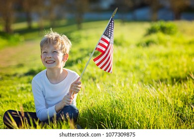 positive little boy with american flag celebrating 4th of july, independence day, or memorial day