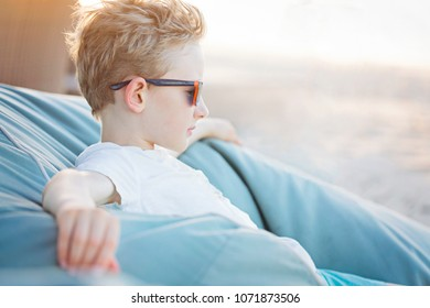 positive little boy relaxing at bean bag, enjoying vacation and being thinkful
